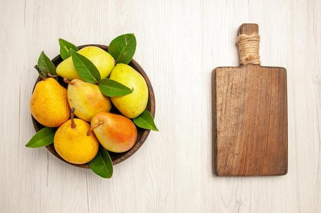 Вид сверху свежие спелые груши сладкие фрукты внутри тарелки на белом столе фрукты желтые свежие сладкие спелые