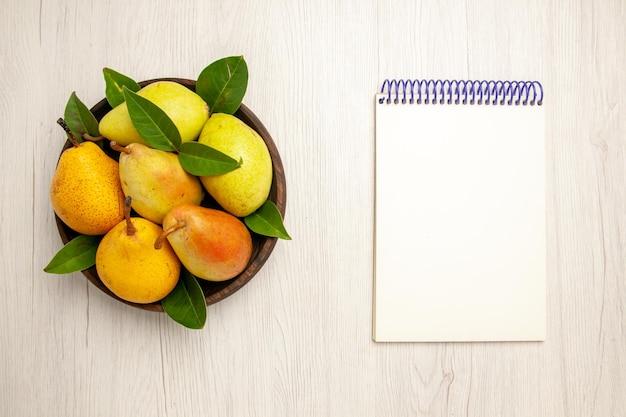 Vista dall'alto pere fresche e dolci frutti dolci all'interno del piatto sulla scrivania bianca frutti gialli freschi dolci maturi