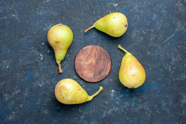 Top view of fresh mellow pears whole ripe and sweet fruits lined on grey desk, fruit mellow food health