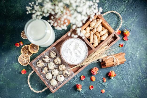 上面図紺色の背景に卵とナッツと新鮮なミルクを焼くケーキビスケットパイ茶生地パンペストリー砂糖