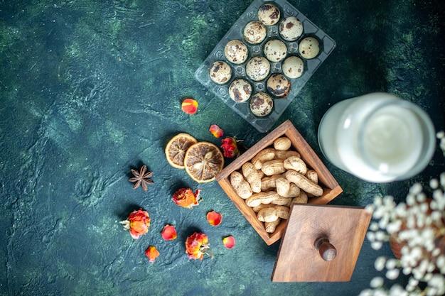 ダークブルーの背景に卵とナッツの入った新鮮なミルクの上面図パイビスケットティーシュガーケーキ写真デザートクッキー