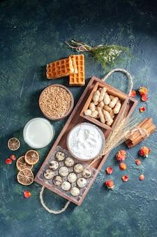 ダークブルーの背景にナッツと卵の入った新鮮なミルクを上から見た図ベイクケーキビスケットパイティー生地パンペストリーシュガー