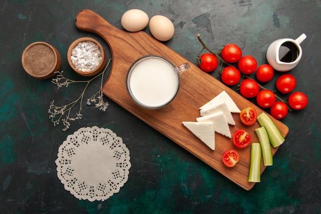 暗い表面に生卵とフレッシュトマトを添えた新鮮な牛乳の上面図野菜ミールフード朝食