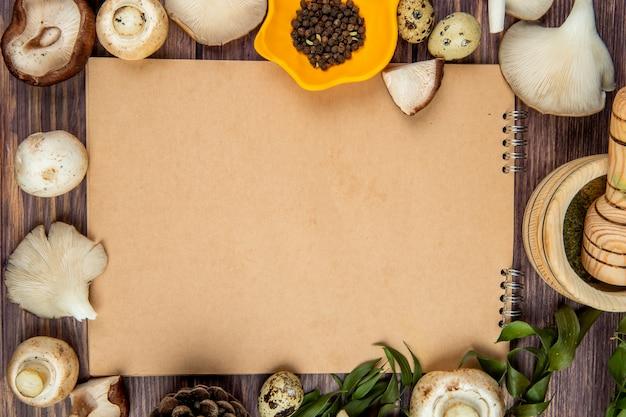 Top view of fresh mushrooms black peppercorns arranged around a sketchbook on rustic wood