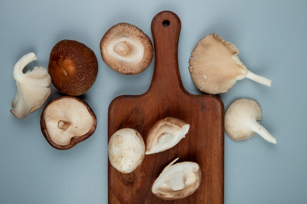 Top view of fresh mushrooms on a wood cutting board on light blue