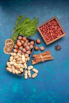 파란색 배경에 있는 접시 안에 있는 신선한 견과류 계피 헤이즐넛과 땅콩이 있는 상위 뷰 호두 색상 스낵 cips 사진 식물 나무 너트