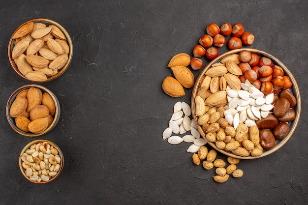 Top view of fresh nuts peanuts and other nuts on a dark surface