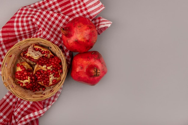 Top view of fresh open pomegranates on a bucket on a checked cloth with copy space