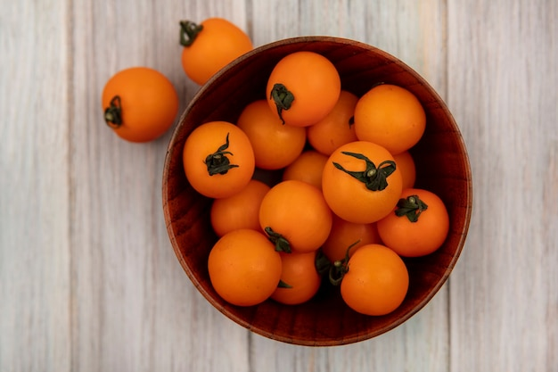 Top view of fresh orange cherry tomatoes on a wooden bowl on a grey wooden surface