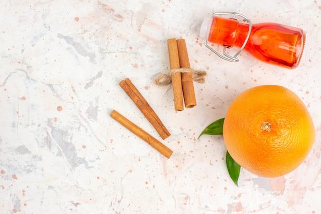 Bottiglia arancione fresca dei bastoncini di cannella di vista superiore sulla superficie luminosa con lo spazio della copia