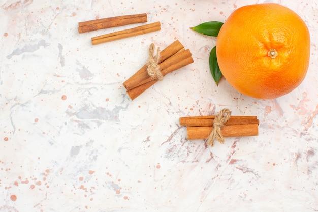 Вид сверху свежие апельсиновые палочки корицы на яркой поверхности с копией пространства
