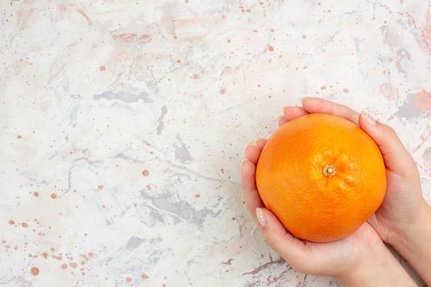 明るい孤立した表面の自由空間に女性の手で新鮮なオレンジの上面図