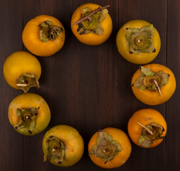 Top view of fresh orange organic persimmon fruits with leaves isolated on a wooden table with copy space