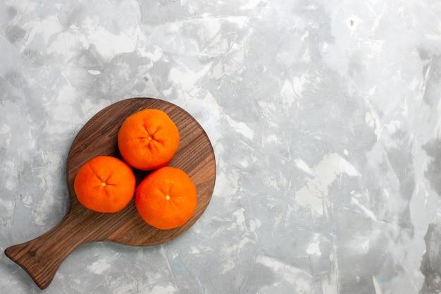 Vista dall'alto mandarini arancioni freschi interi agrumi acidi e pastosi su sfondo bianco chiaro.