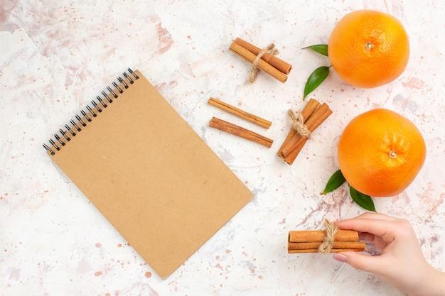Вид сверху свежие апельсины палочки корицы блокнот на яркой поверхности