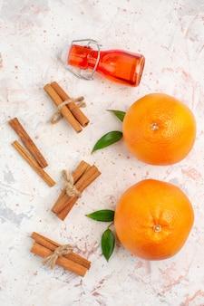 Vista dall'alto arance fresche bastoncini di cannella bottiglia sulla superficie luminosa