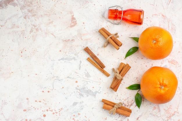 Вид сверху свежие апельсины бутылка палочки корицы на светлой поверхности свободное пространство