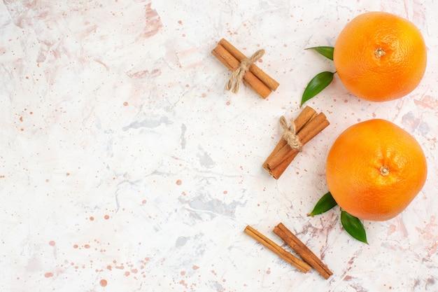 Vista dall'alto arance fresche bastoncini di cannella sulla superficie luminosa con posto libero