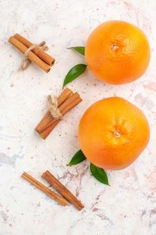 Vista dall'alto arance fresche bastoncini di cannella sulla superficie luminosa