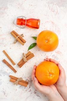 Vista dall'alto arance fresche bastoncini di cannella in mano femminile bottiglia sulla superficie luminosa