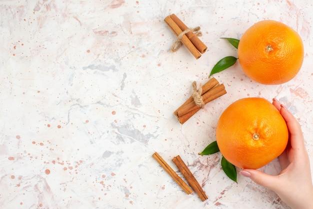 Vista dall'alto arance fresche bastoncini di cannella arancione in mano femminile su superficie luminosa con copia posto
