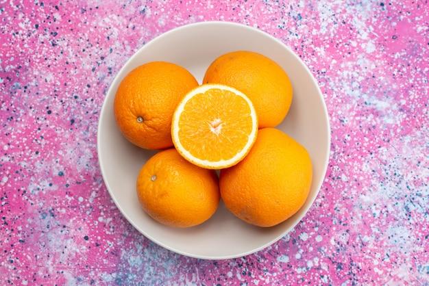 Vista dall'alto arance fresche all'interno della piastra sullo sfondo colorato di frutta fresca di agrumi esotici