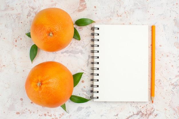 Matita arancione del taccuino delle arance fresche di vista superiore sulla superficie isolata luminosa