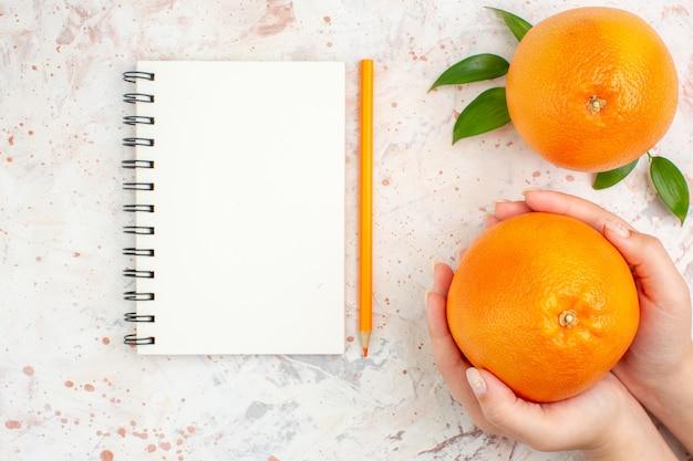 Вид сверху свежие апельсины блокнот оранжевый карандаш женская рука на яркой изолированной поверхности