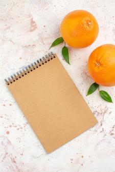 Vista dall'alto arance fresche un blocco note sulla superficie luminosa