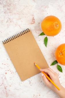 Vista dall'alto arance fresche una matita arancione del blocco note in mano femminile sul posto libero superficie luminosa