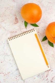 Vista dall'alto arance fresche arancione matita sul blocco note sulla superficie luminosa