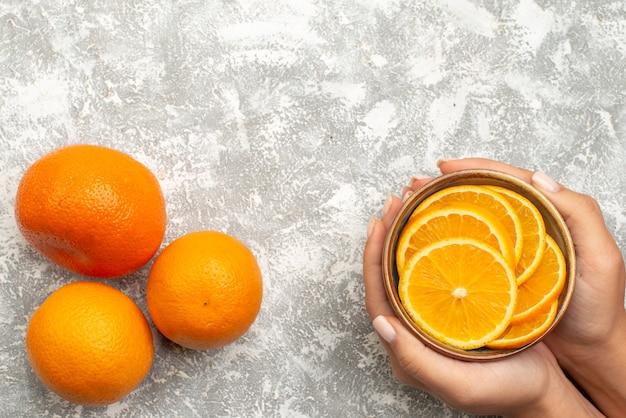 Vista dall'alto arance fresche affettate e frutti interi su fondo bianco agrumi esotici succo di frutta tropicale