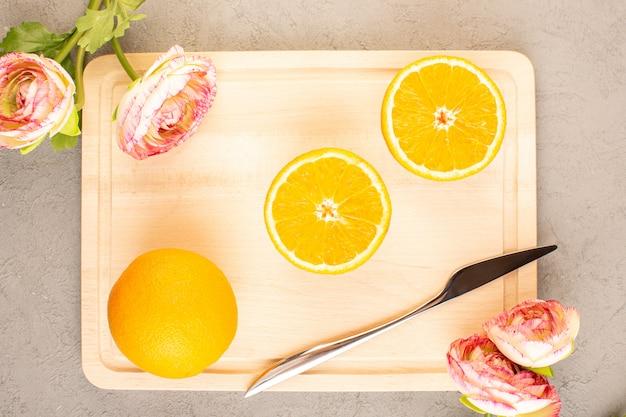 Una vista dall'alto di arance fresche acide maturi affettati e interi agrumato dolce tropicale con rose secche vitamine gialle sulla scrivania color crema