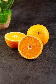 A top view fresh oranges sour ripe whole and sliced mellow citrus tropical vitamine yellow on the dark desk