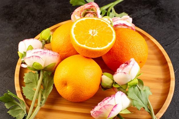 Una vista dall'alto arance fresche acide mature intere e affettate agrumato dolce tropicale giallo vitamina sulla scrivania scura