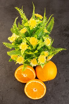 A top view fresh oranges sour ripe whole and sliced plants mellow citrus tropical vitamine yellow on the dark desk
