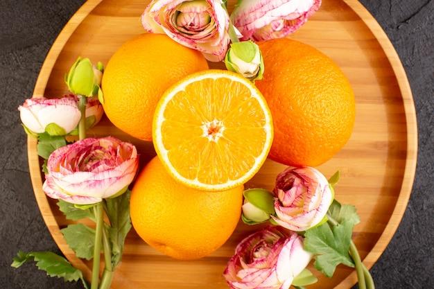 Una vista dall'alto di arance fresche acide mature intere e affettate con rose secche agrumi gialli tropicali vitamina giallo sulla scrivania scura