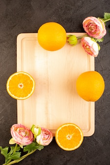 A top view fresh oranges sour ripe whole with dried roses mellow citrus tropical vitamine yellow on the dark desk