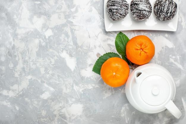 明るい白の背景にやかんとチョコレートケーキとトップビューの新鮮なオレンジフルーツ柑橘類新鮮なエキゾチックな熱帯