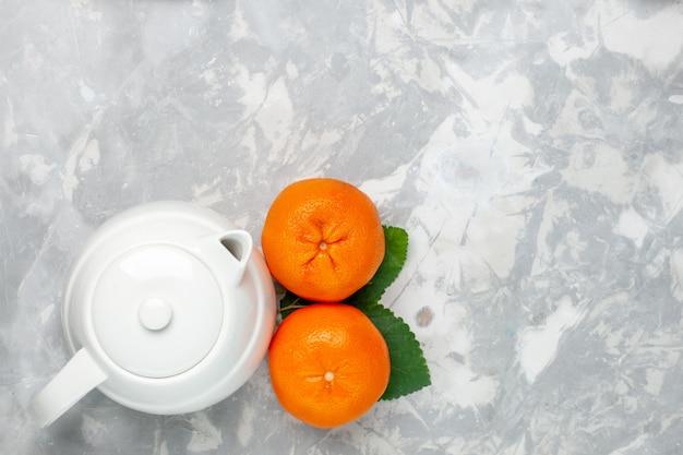 平面図明るい白の背景にやかんと新鮮なオレンジフルーツ柑橘類新鮮なエキゾチックな熱帯