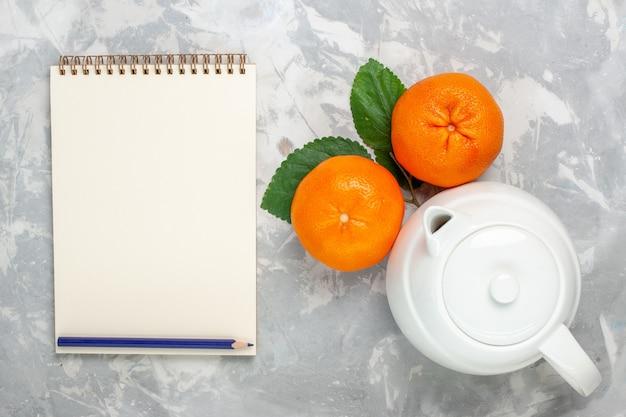 Вид сверху свежие апельсины с чайником на светло-белом фоне фрукты цитрусовые свежие экзотические тропические