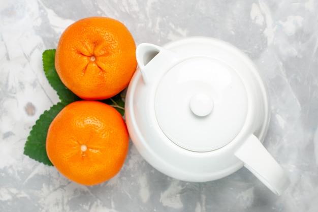 Vista dall'alto di arance fresche con bollitore su superficie bianca agrumi freschi esotici tropicali