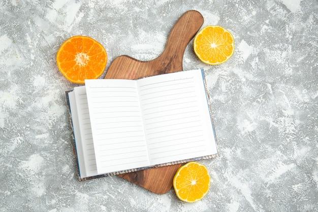 エキゾチックな白い表面のフルーツ柑橘類にメモ帳でトップビューの新鮮なオレンジ