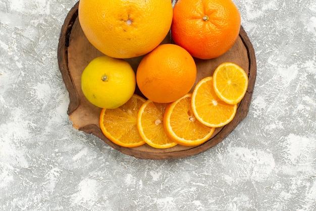 上面図白い机の上にみかんと新鮮なオレンジ柑橘類のエキゾチックな熱帯の新鮮な果物