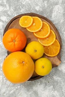 Vista dall'alto arance fresche con mandarini su superficie bianca agrumi esotici frutta fresca tropicale