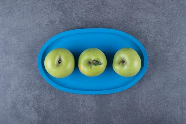 Vista dall'alto di mele verdi organiche fresche sul piatto di legno blu