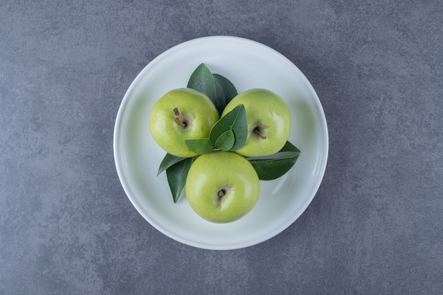 Top view of fresh organic green apples on white plate