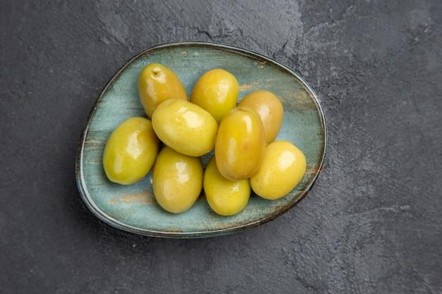Вид сверху свежие органические зеленые оливки на синей тарелке на темном фоне