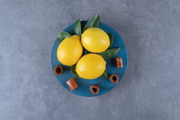 Top view of fresh organic lemons and leaves.