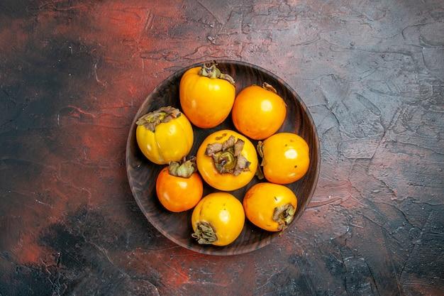 Vista dall'alto di diospyros kaki giallo naturale organico fresco su un piatto marrone
